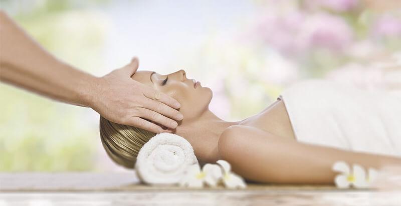 žena ležící na zádech s hlavou podepřenou stočeným ručníkem při masáži obličeje