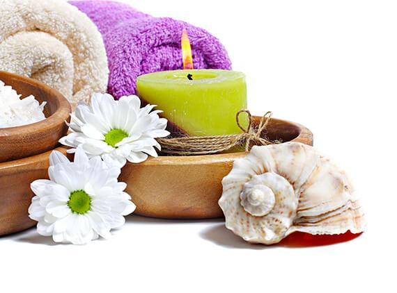 dva stočené ručníky před hořící zelenou svíčkou a mušlí